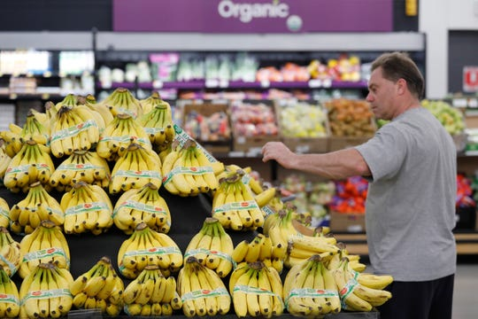 A customer shops for bananas at a Walmart Neighborhood Market, Wednesday, April 24, 2019, in Levittown, N.Y.
