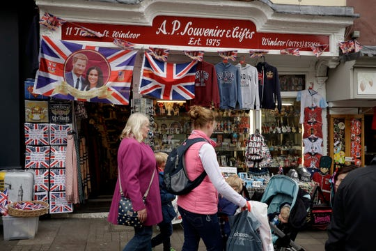 A British Union flag bearing an image of Prince Harry and Meghan, the Duchess of Sussex, is displayed outside a shop in Windsor, England, Tuesday, April 16, 2019.