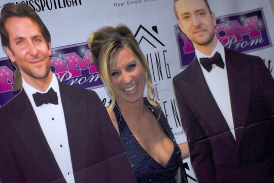 """Wearing her Canton High School Prom dress from 2001, Michelle Milne of Westland poses for photos with her """"prom dates"""" Bradley Cooper, left, and Justin Timberlake."""