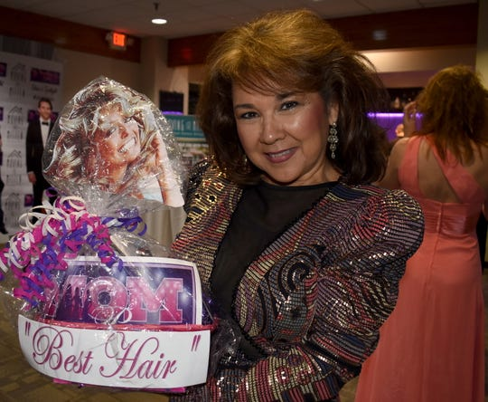 "Deanna Ledesma of Bay City shows off the Farrah Fawcett-topped gift basket she scored for winning the ""Aqua Net Best Hair"" contest."