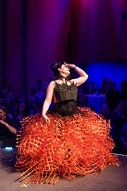 """""""Dystopian Incubation,"""" designed and modeled by Michelle Beiling in the 2018 ReCouture runway show. The look is made out of drinking straws and deer fencing."""