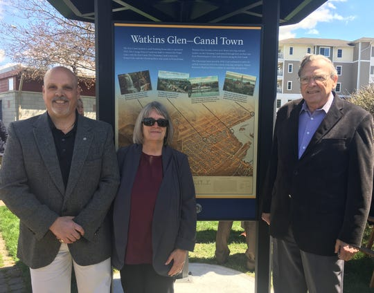 A new sign at Seneca Harbor Park in Watkins Glen recognizes the importance of the Erie Canal to Schuyler County's early economic development. At the sign unveiling ceremony are, from left, Watkins Glen Trustees Lou Perazzini and Nan Shaw, and Montour Falls Mayor John King.