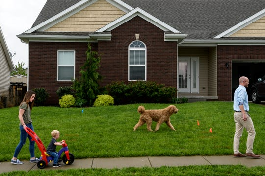 Erin Johnson, from left, helps her two-year-old son Henry roll along the sidewalk as they take a walk in front of their house with the family dog, Oliver, and husband Adam Johnson in Evansville, Ind., Thursday, April 25, 2019. Erin and Adam, who grew up in Fort Branch, bought the home in March 2018 and moved back to the area from Indianapolis.