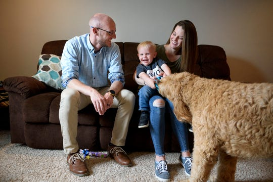 """The Johnson family, from left, Adam, two-year-old Henry, Erin and their five-year-old dog Oliver laugh together as Henry and Oliver play tug of war at their home in Evansville, Ind., Thursday, April 25, 2019. The population of Evansville and its surrounding region is stagnant, but the city's recent home-buying statistics placed it atop a Realtor.com top 10 list of """"Hottest Cities for Young Millennials."""""""