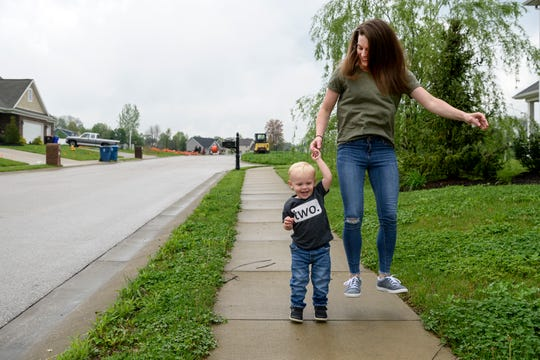 Two-year-old Henry Johnson and his mother Erin Johnson practice their hopping skills as they stroll along a street in the neighborhood of their northern Vanderburgh County home, Thursday afternoon, April 25, 2019. Erin and her husband Adam both grew up in Fort Branch and decided to move back to the area in 2018 after a stint of living in Indianapolis.