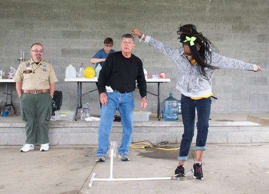 Thompkins Elementary seventh-grader Octaiva Mason, right, stomps on a POP! Rocket to launch a plastic battle in the air as Boy Scouts of America Chaplin Mark Dicken, left, and Evansville Museum's Jim Price teach science lessons during the Buffalo Trace Council's Exceptional Needs Field Day at the Eykamp Scout Center Thursday, April 25, 2019. Mason was celebrating her 14th birthday.