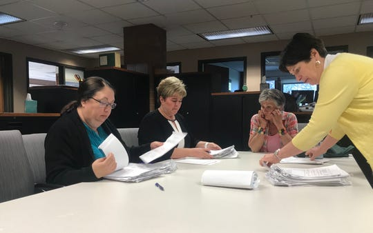 Penny Laviolette, in pink, watches as the City Clerk and her staff county petition packets Thursday afternoon. Laviolette gathered signatures to repeal fire pit restrictions, but believes she fell short of the minimum number needed.