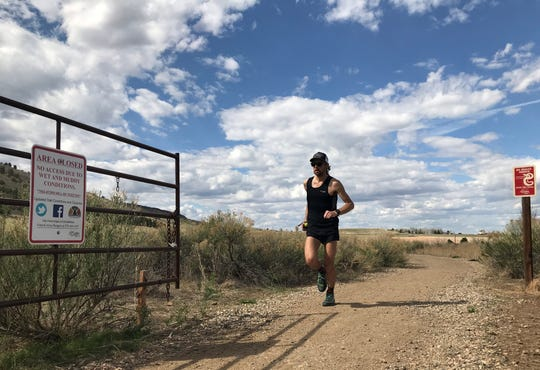 A trail runner emerges from Maxwell Natural Area on Wednesday. Rangers have written 19 tickets for recreationists hiking and biking on Maxwell's trails since March 9.