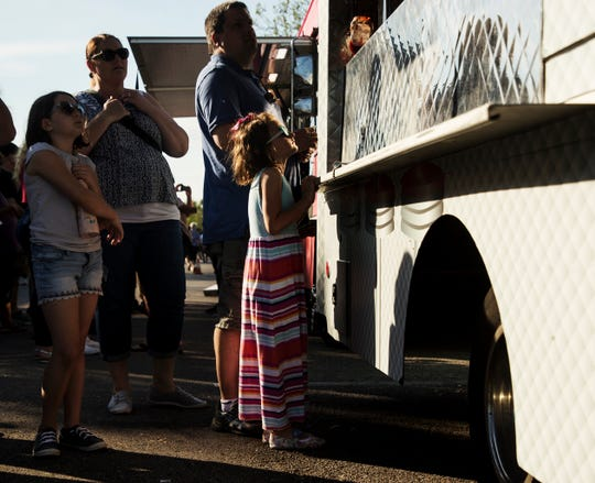 Charlotte Walsh, 6, orders food from the Rolling Indulgence truck with her parents, Erin and Tom along with sister Hannah, 9. Food trucks from the The Food Network's 'The Great Food Truck Race' were at the Fort Myers Brewing Co. in Fort Myers on Wednesday April, 24, 2019. The show has been shooting in the Fort Myers area over the last several days.