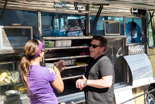 Tyler Florence of the Food Network's 'The Great Food Truck Race' jokes with a contesant from NOLA Creations 504 food truck while attending an event at the Fort Myers Brewing Co. in Fort Myers on Wednesday April, 24, 2019. The show has been shooting in the Fort Myers area over the last several days.