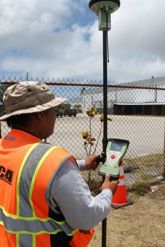 "Charles Untalan, chief of survey for Duenas, Camacho and Associates, on April 25 holds a ""rover"" outside the fence at Simon Sanchez High School. The device uses global positioning to identify points for land surveys. It is accurate to within 2 millimeters. The company on Thursday started identifying the boundaries of the school property as the first phase of a project to build a new school."
