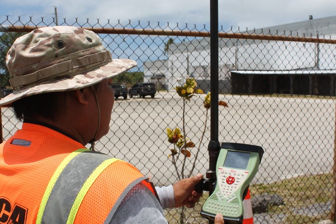 "Charles Untalan, chief of survey for Duenas, Camacho and Associates, on April 25, 2019, holds a ""rover"" outside the fence at Simon Sanchez High School. The device uses global positioning to identify points for land surveys. It is accurate to within 2 millimeters. The company  started identifying the boundaries of the school property as the first phase of a project to build a new school."
