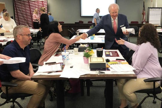 Joel Hopper (center) shakes hands Tuesday to congratulate Spottsville Elementary School Principal Sarah Estabrook (at left) and Jefferson Elementary Principal Crissy Sandefur. The two principals recently graduated from the Kentucky Chamber Foundation's Leadership Institute for School Principals, of which Hopper is co-chair.