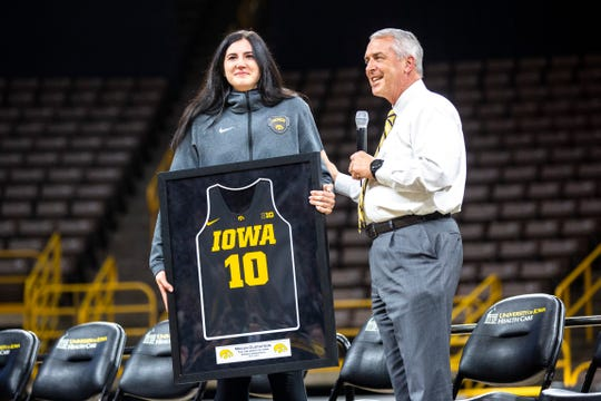 Iowa center Megan Gustafson (10) smiles while Iowa athletic director Gary Barta, right, announced he was retiring her jersey during a celebration of the 2018-19 Hawkeyes women's basketball season, Wednesday, April 24, 2019.