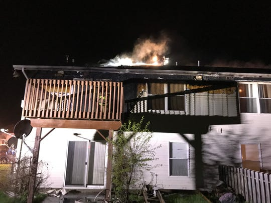 A fire smolders from the roof of a residence Thursday morning, April 25, 2019, in North Liberty.