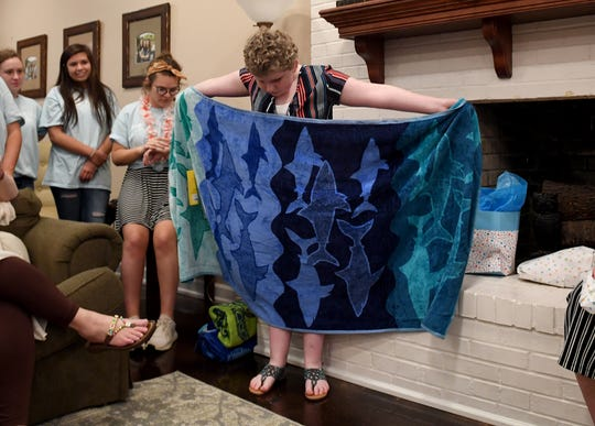 Members of Chi Omega at Union University watch as 10-year-old Jay-da Dedmon opens one of her gifts after her wish to swim with dolphins was granted, Thursday, April 25.