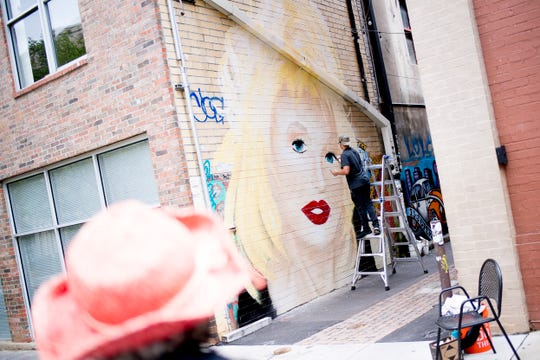 Artist Colton Valentine paints a mural of Dolly Parton in Strong Street Alley in Knoxville in Tennessee on Friday, April 19, 2019.