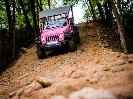 A Pink Jeep Tours Jeep drives down a hill during a ride at a Pink Jeep Tours grand opening event held in Pigeon Forge on Thursday, April 25, 2019.