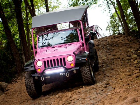 A Pink Jeep Tours vehicle drives down a hill during a ride in Pigeon Forge, Tenn., on April 25.