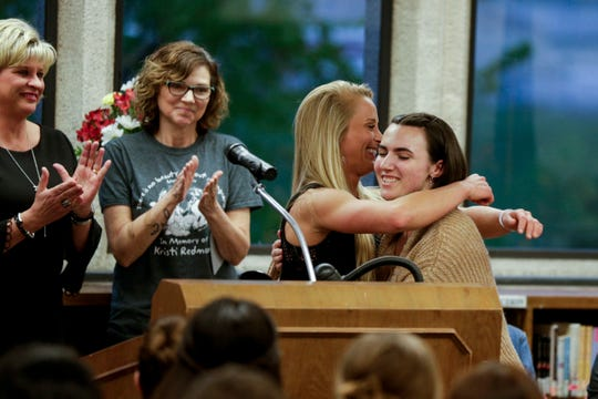 Maggie Huston, right, embraces Arielle Redmon as she receives the first Kristi Redmon Scholarship, Thursday, April 25, 2019 at Lafayette Jefferson High School in Lafayette. Kristi Redmon, Arielle's mother, an elementary school art teacher, was killed in her Lafayette home in Oct. 2016.