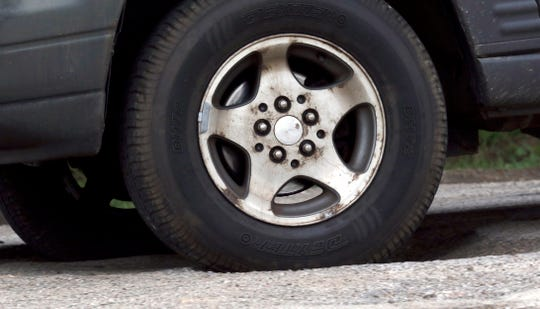 The tire of a vehicle sinks into a pothole on River Way Drive Tuesday afternoon, April 23, 2019, in Lancaster. Residents and business owners along the private road met with a representative of the road's owner in a private meeting mediated by the city Tuesday.