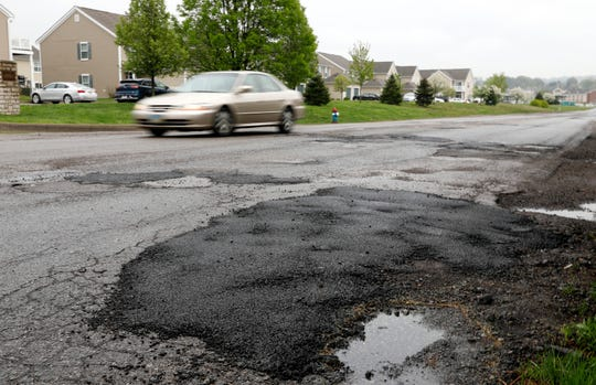 A car is driven past freshly patched potholes Thursday morning, April 25, 2019, on River Way Drive in Lancaster.