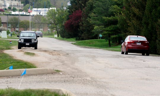 A vehicle is driven fully off of River Way Drive to avoid potholes Tuesday afternoon, April 23, 2019, in Lancaster. Residents and business owners along the private road met with a representative of the road's owner in a private meeting mediated by the city Tuesday.