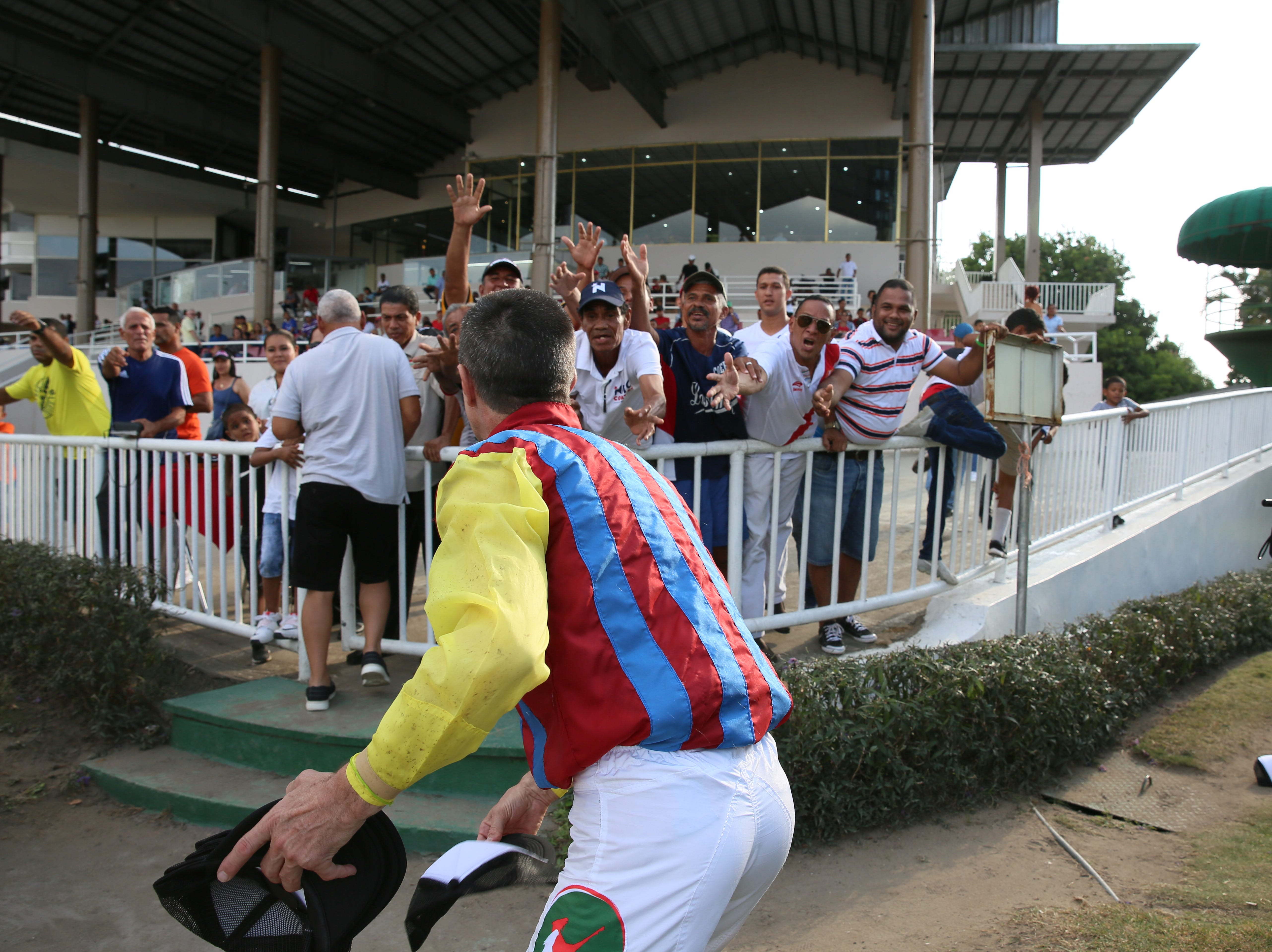 A winning jockey throws a hat to the crowd at Panama's only racetrack