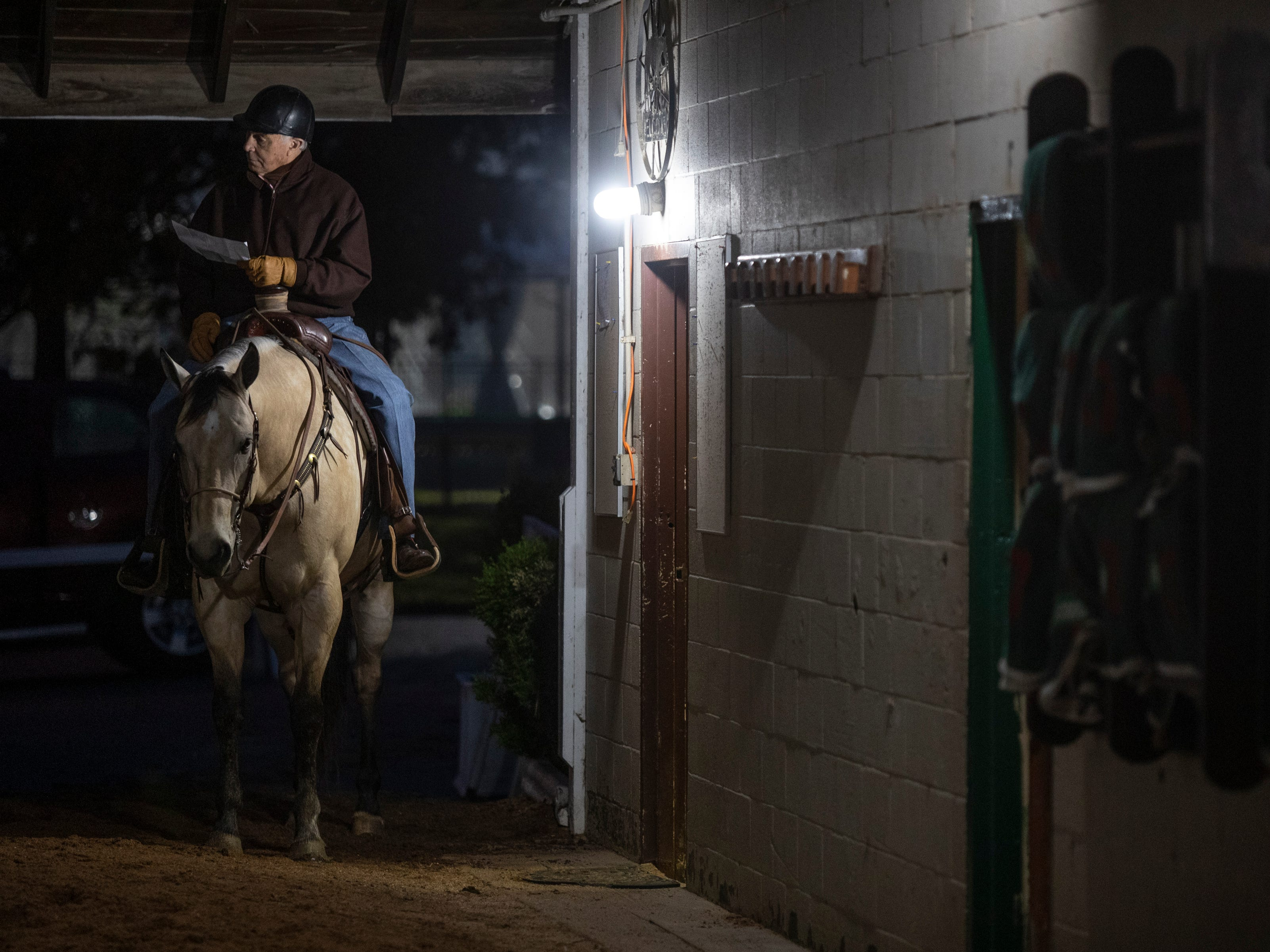 "84 year-old Hall of Fame horse trainer D. Wayne Lukas checks some paper work from atop his horse, ""Starbuck,"" before leading his thoroughbreds to the track for morning workouts at Churchill Downs. April 25, 2019."