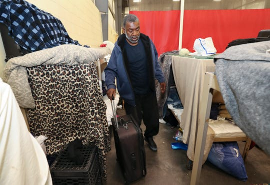 Noel Langdon Sr. packs some belongings at the low-barrier shelter inside the Wayside Christian Mission.