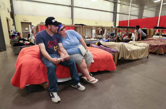 Jason Lucas, left, and his wife Sally Lucas relax on their bed in the low-barrier shelter inside the Wayside Christian Mission rescue station. They are residents and Jason also works security there.