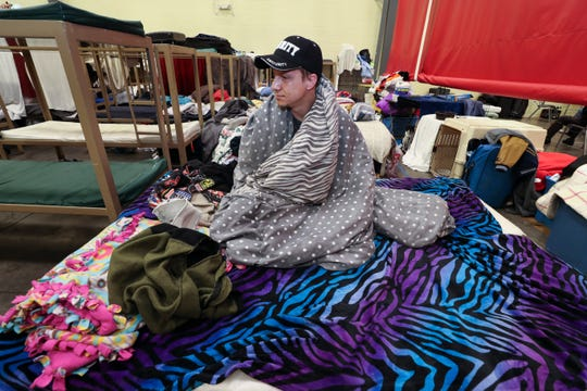 Brent Hagan relaxes on his bed in the low-barrier shelter inside the Wayside Christian Mission rescue station. He is a resident and also works security there.