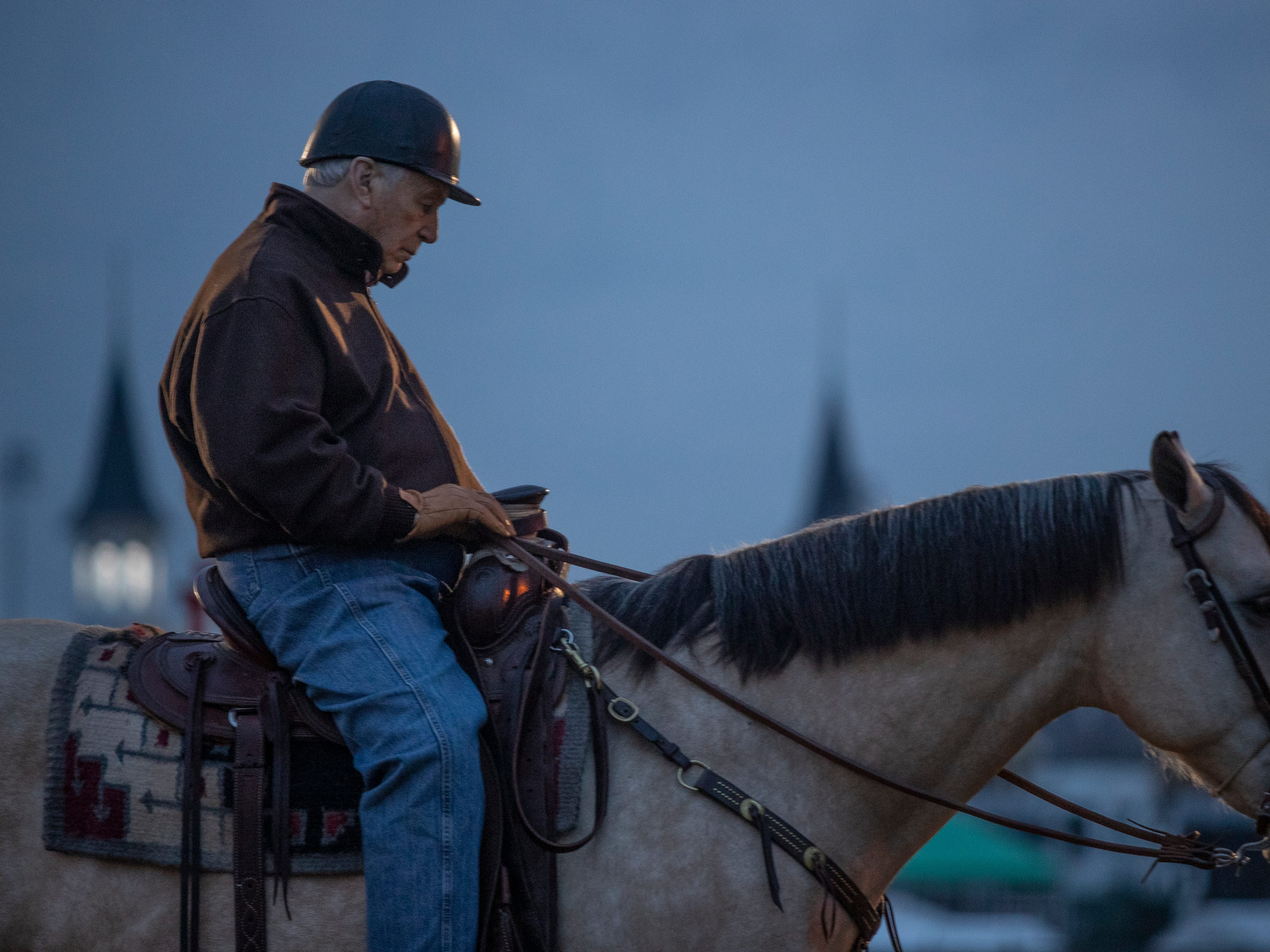 "84 year old Hall of Fame trainer D. Wayne Lukas sat on ""Starbuck"" with the twin spires of Churchill Downs in the background, while watching his horses train. April 25, 2019."