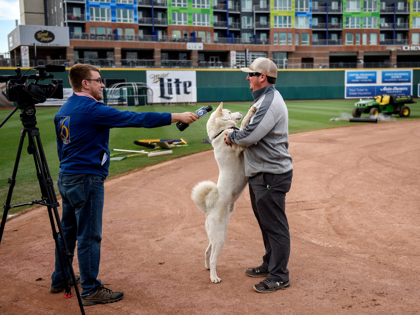 Lugnuts Head Groundskeeper Zach Severns get an impromptu visit from his dog Chief while Severns is interviewed by a television reporter as a crew works to turnover the baseball field for a Lansing Ignite soccer match on Wednesday, April 24, 2019, at Cooley Law School Stadium in Lansing.