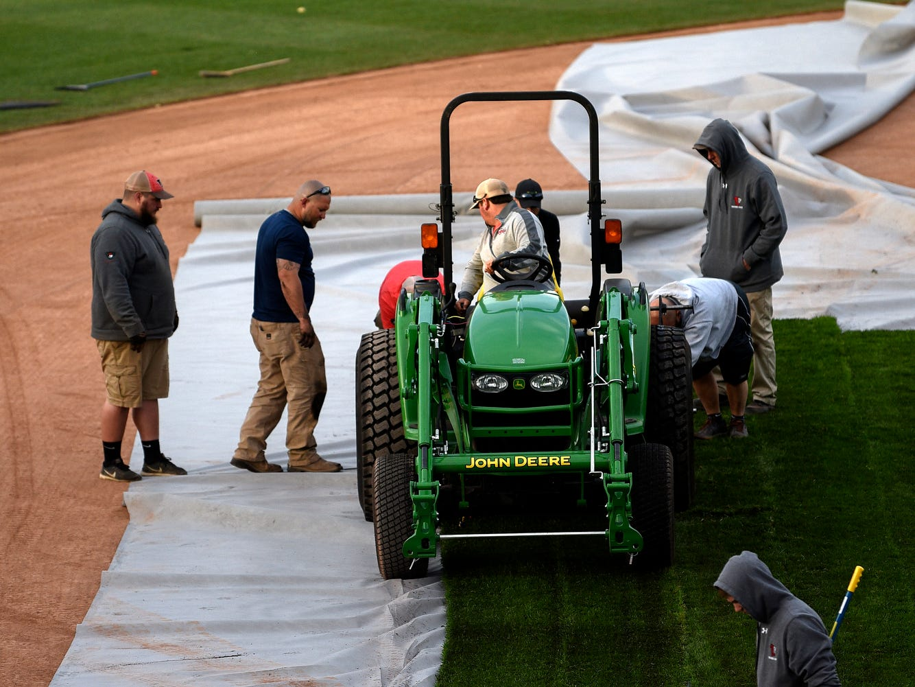 A crew lays sod on the infield dirt as the Lugnuts baseball field is transformed into a soccer pitch on Wednesday, April 24, 2019, before an upcoming Lansing Ignite soccer match at Cooley Law School Stadium in Lansing.