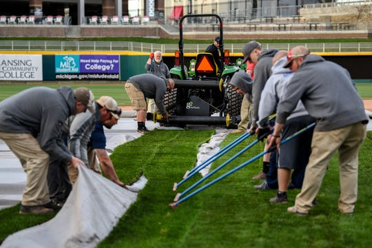A crew works to fit 80-foot pieces of sod that were placed over the baseball infield with the assistance from a tractor as the Lugnuts field is transformed into a soccer pitch on Wednesday, April 24, 2019, at Cooley Law School Stadium in Lansing.