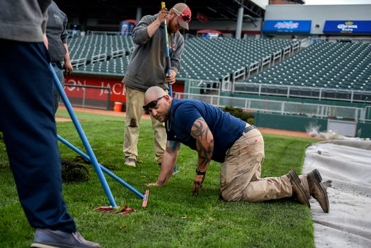 Derek Trueblood, with J&D Turf, works with a crew to turnover the Lugnuts baseball field for a Lansing Ignite soccer match on Wednesday, April 24, 2019, at Cooley Law School Stadium in Lansing.
