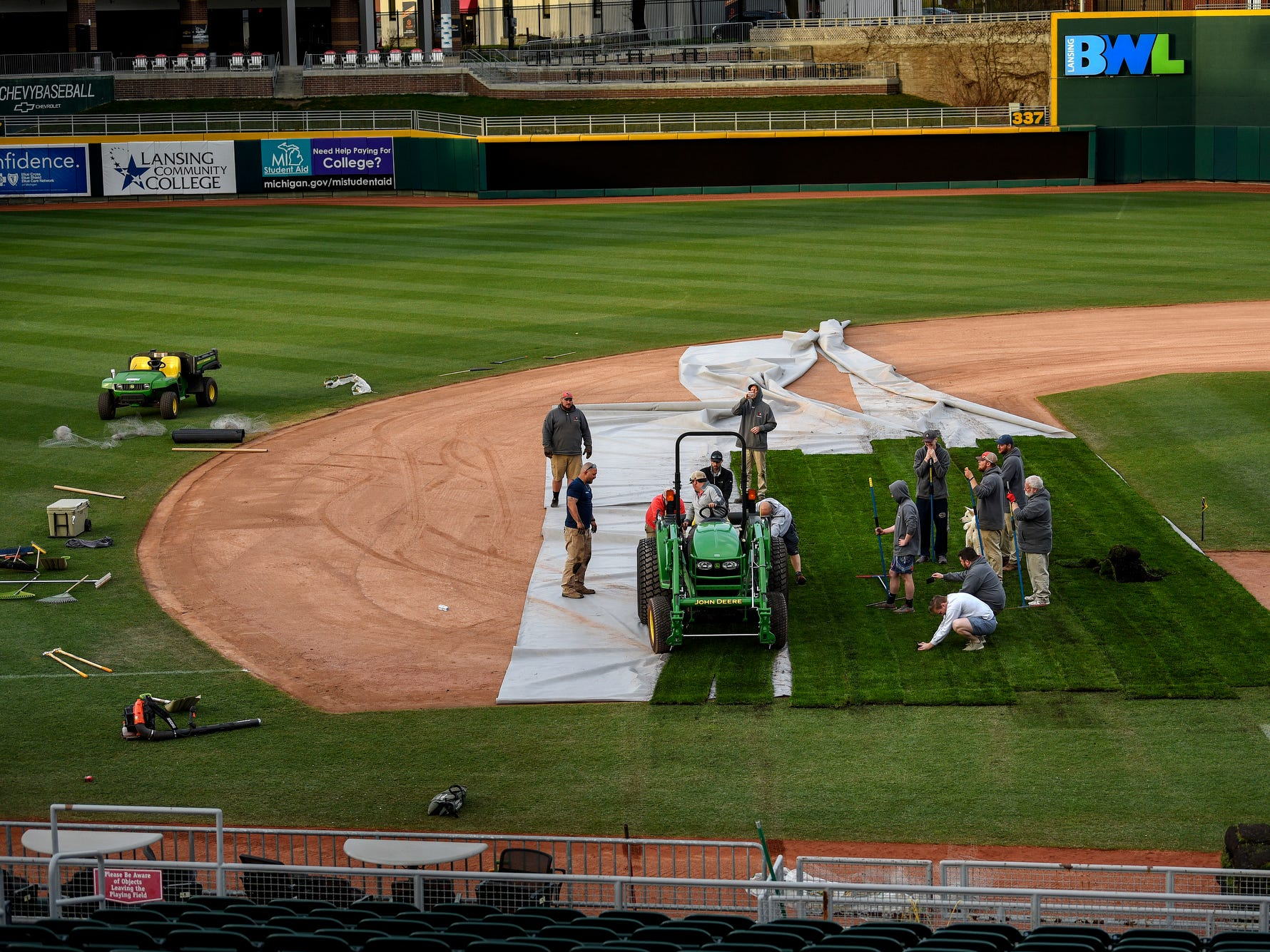 A crew works to transform the Lugnuts baseball field into a soccer pitch on Wednesday, April 24, 2019, before an upcoming Lansing Ignite soccer match at Cooley Law School Stadium in Lansing.