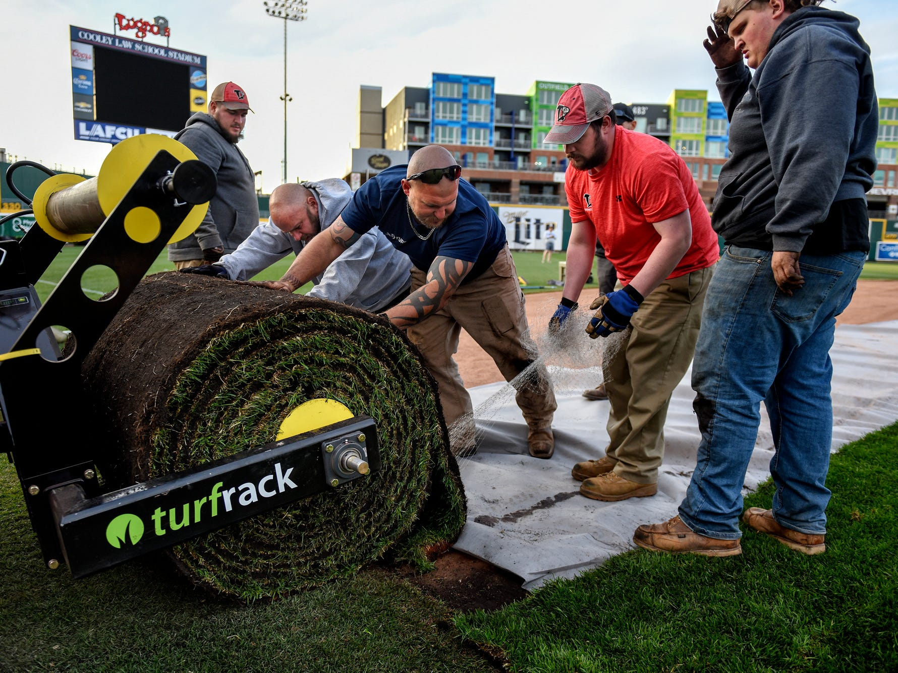 A crew carefully unrolls a spool of sod with assistance from a tractor while workers turnover the Lugnuts baseball field for a Lansing Ignite soccer match on Wednesday, April 24, 2019, at Cooley Law School Stadium in Lansing.