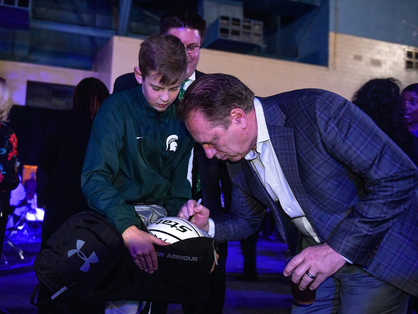 Michigan State University men's basketball coach Tom Izzo, right, signs a basketball for Ben Sumnar, 13, during the fifth-annual Lansing Promise Dinner on Thursday, April 25, 2019, at the Don Johnson Fieldhouse in Lansing. Ben was attending the event with his father Mike who is a supporter of the cause.