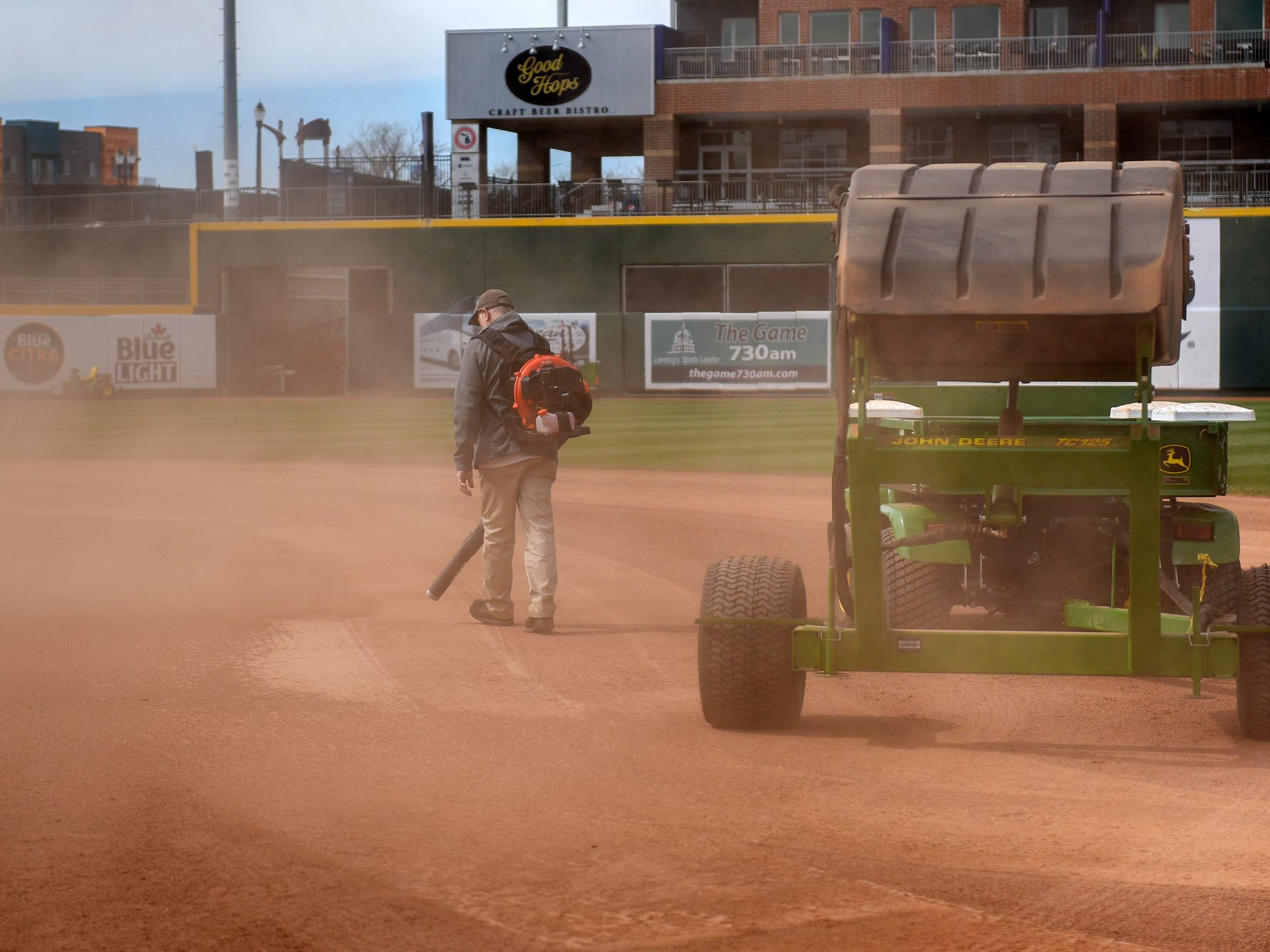 A grounds crew member uses a blower on the infield dirt as the Lugnuts baseball field is transformed into a soccer pitch on Wednesday, April 24, 2019, before an upcoming Lansing Ignite soccer match at Cooley Law School Stadium in Lansing.