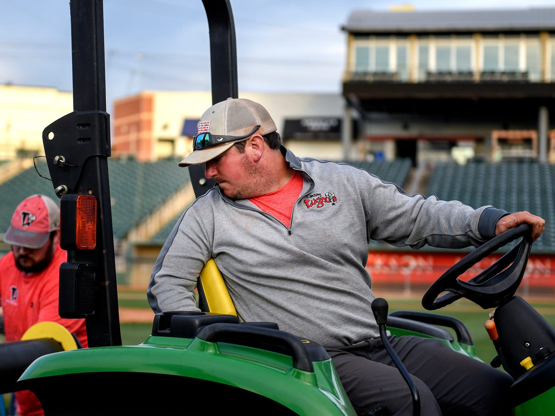 Lugnuts Head Groundskeeper Zach Severns carefully drives a tractor to unroll a spool of sod he and a crew works to turnover the baseball field for a Lansing Ignite soccer match on Wednesday, April 24, 2019, at Cooley Law School Stadium in Lansing.