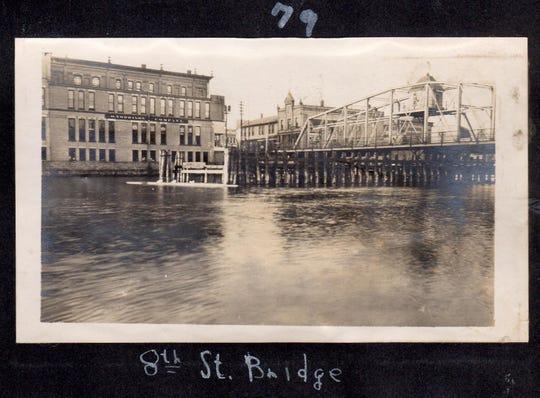 Eighth Street bridge in Manitowoc with O. Torrison Store at left, and at right is the Post Office, offices for Pere Marquette RR, C. Reiss Coal Co., Roberts Drug Store and Liebenow Jewelers.