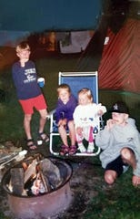 Chelsey Lewis (center left, in purple) roasts marshmallows over a campfire with her siblings and a family friend at Yogi Bear's Jellystone Park in Baraboo in 1995.