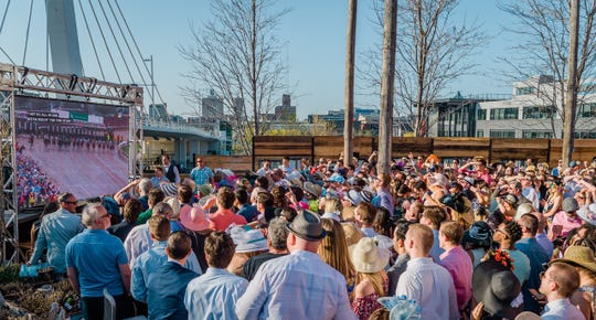 Party-goers watch the Kentucky Derby on a giant screen at the Iron Horse Hotel.