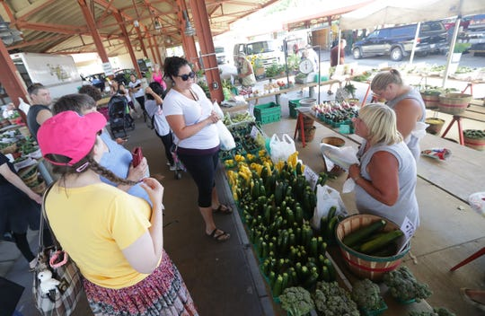 Customers gather around Cindy's Greenhouse and Fresh Vegetables, out of East Troy, while owner Cindy Chapman (second from right) and her daughter, Jessie Stocchetti, assist their customers last year at the West Allis market.
