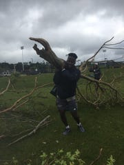 Louisiana Tech football player Praise Okorie helps clean up debris at the La. Tech soccer stadium.