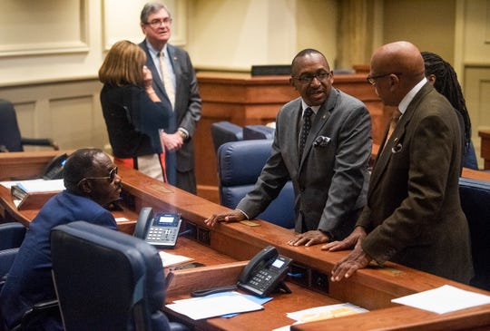 Sen. Bobby Singleton, center, talks with Sen. David burette, left, and Sen. Rodger Smitherman, right, on the senate floor in the Alabama Statehouse in Montgomery, Ala., on Thursday April 25, 2019.