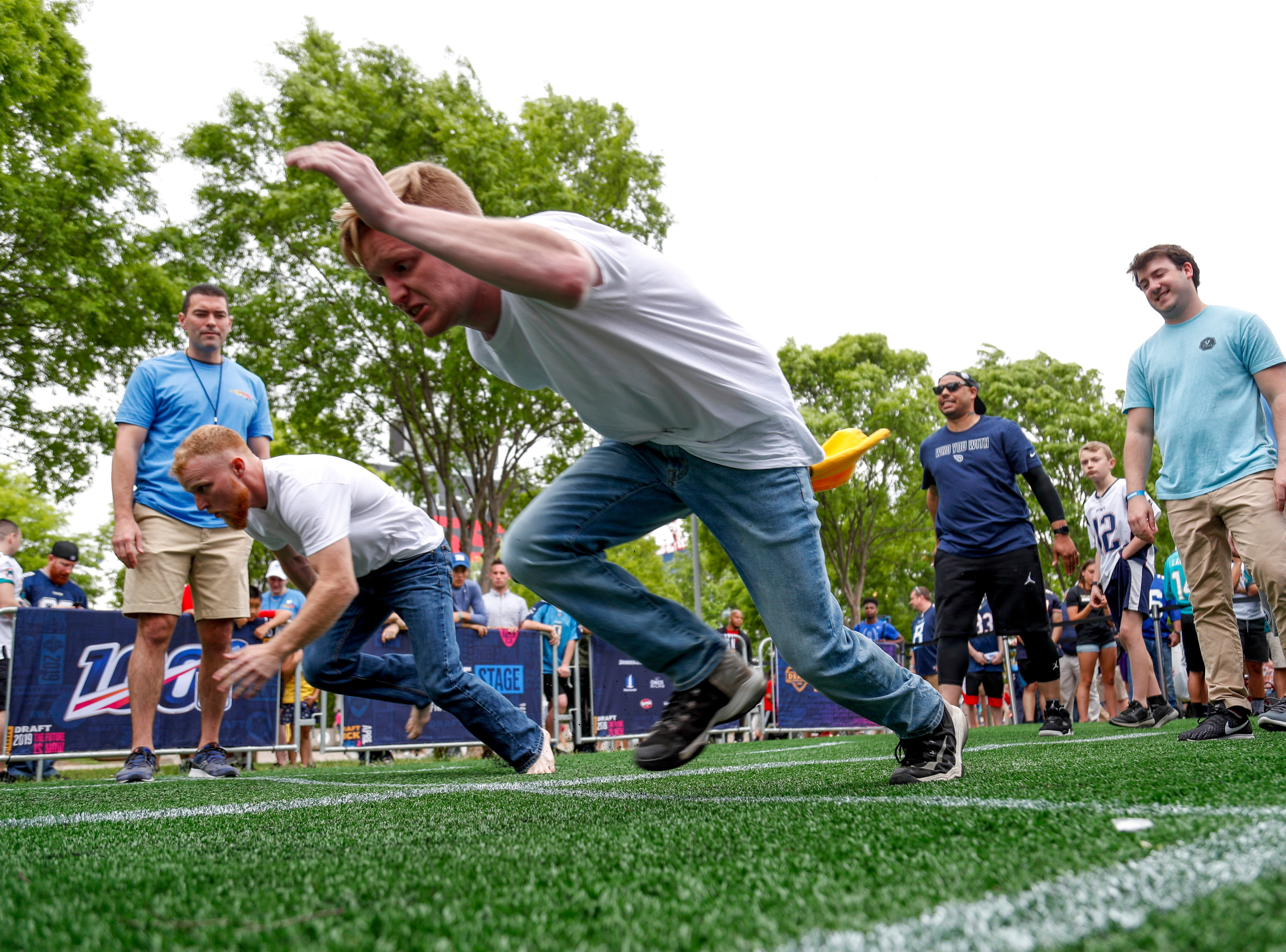 Fans charge from the starting line at the 40 yard dash during the NFL Draft Experience at Nissan Stadium in Nashville, Tenn., on Thursday, April 25, 2019.