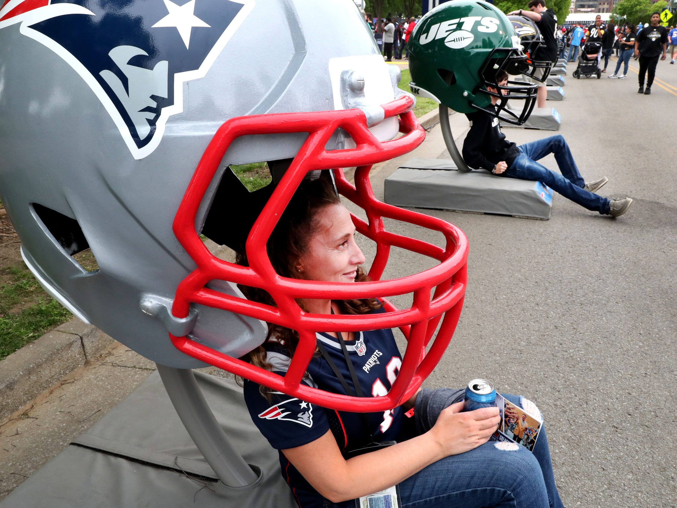 Sherri Woodward from Rhode Island gets her picture taken inside an oversized New England Patriots helmet at the NFL Draft Experience, at Nissan Stadium on Thursday, April 25, 2019, in Nashville, Tennessee.
